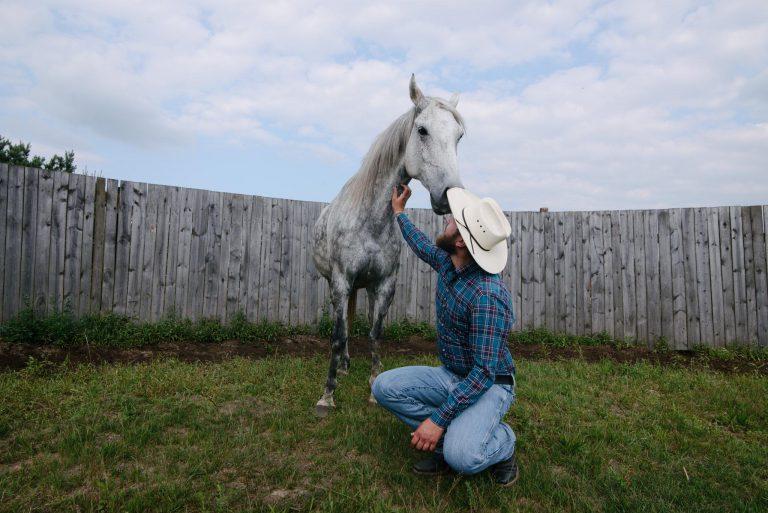 Mężczyzna kucający przed koniem na roundpenie