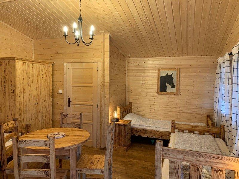 Domek czteroosobowy - widok na łóżka i drzwi do łazienki